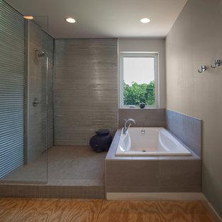 На фото: главные ванные комнаты в стиле модернизм с накладной ванной, открытым душем, серой плиткой, керамической плиткой, серыми стенами, полом из фанеры и столешницей из плитки