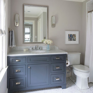 Elegant bathroom photo in Minneapolis with shaker cabinets, blue cabinets, a two-piece toilet, gray walls, an undermount sink and marble countertops