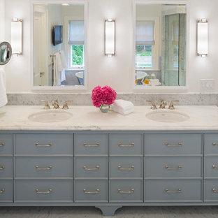 Idee per una stanza da bagno padronale tradizionale con consolle stile comò, ante blu, pareti bianche, lavabo sottopiano e top in marmo