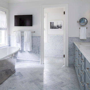 Elegant master multicolored tile and marble tile freestanding bathtub photo in Minneapolis with furniture-like cabinets, blue cabinets, white walls, an undermount sink and marble countertops