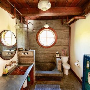 Inspiration för mellanstora industriella grått badrum med dusch, med öppna hyllor, skåp i mellenmörkt trä, en öppen dusch, en toalettstol med separat cisternkåpa, gula väggar, ett undermonterad handfat, ett platsbyggt badkar, betonggolv, bänkskiva i rostfritt stål, med dusch som är öppen, porslinskakel och brunt golv