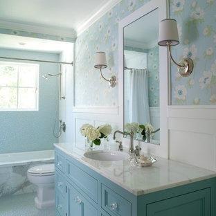 サンフランシスコの中くらいのトラディショナルスタイルのおしゃれな浴室 (青いキャビネット、アンダーマウント型浴槽、青いタイル、青い壁、大理石の洗面台、アンダーカウンター洗面器、落し込みパネル扉のキャビネット、シャワー付き浴槽、石タイル、玉石タイル、白い洗面カウンター) の写真