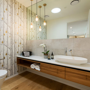 Mid-sized contemporary bathroom in Other with flat-panel cabinets, medium wood cabinets, gray tile, porcelain tile, multi-coloured walls, medium hardwood floors, a vessel sink, brown floor and white benchtops.