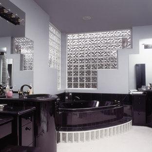 Mittelgroßes Modernes Badezimmer En Suite mit flächenbündigen Schrankfronten, schwarzen Schränken, Eckbadewanne, schwarzen Fliesen, grauer Wandfarbe, Einbauwaschbecken und Mineralwerkstoff-Waschtisch in Dallas