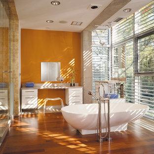 Ispirazione per una stanza da bagno padronale industriale con vasca freestanding, pareti arancioni, ante bianche, pavimento in legno massello medio e pavimento marrone