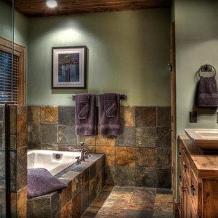 Imagen de cuarto de baño principal, rural, con puertas de armario con efecto envejecido, bañera encastrada, ducha esquinera, baldosas y/o azulejos de pizarra, paredes verdes, suelo de pizarra, lavabo sobreencimera, encimera de madera, ducha con puerta con bisagras y suelo multicolor