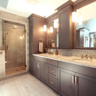 Пример оригинального дизайна: большая главная ванная комната в стиле современная классика с фасадами с утопленной филенкой, серыми фасадами, душем в нише, раздельным унитазом, разноцветной плиткой, плиткой из листового стекла, серыми стенами, полом из известняка, врезной раковиной, столешницей из искусственного кварца, серым полом, душем с распашными дверями и бежевой столешницей