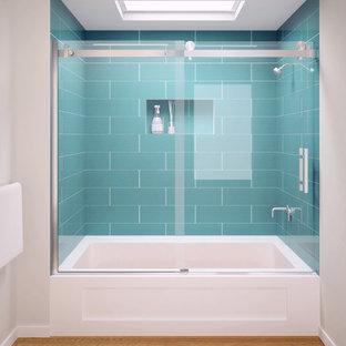 Immagine di un'ampia stanza da bagno padronale chic con vasca ad alcova, doccia alcova, piastrelle blu, piastrelle di vetro, pareti grigie e parquet chiaro