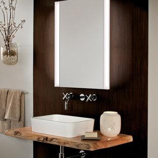 Aménagement d'une très grande salle de bain principale contemporaine avec une vasque, un plan de toilette en bois, un mur beige et un sol en carrelage de céramique.