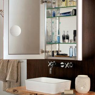 Réalisation d'une très grande salle de bain principale design avec une vasque, un placard à porte vitrée, un plan de toilette en bois, un mur beige et un sol en carrelage de céramique.