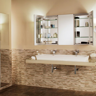 Large transitional master multicolored tile and glass tile ceramic tile bathroom photo in New York with a trough sink, glass countertops and beige walls