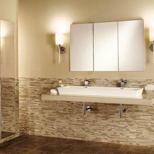 Modelo de cuarto de baño principal, tradicional renovado, grande, con lavabo de seno grande, armarios tipo vitrina, encimera de vidrio, baldosas y/o azulejos multicolor, baldosas y/o azulejos de vidrio, paredes beige y suelo de baldosas de cerámica