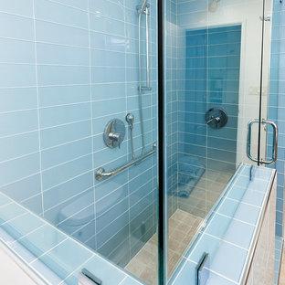 Diseño de cuarto de baño con ducha, retro, pequeño, con armarios con paneles lisos, puertas de armario de madera clara, ducha esquinera, baldosas y/o azulejos de vidrio, paredes beige, suelo de travertino, lavabo bajoencimera, encimera de cuarzo compacto, suelo beige y ducha con puerta con bisagras