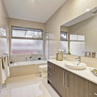 This is an example of a mid-sized contemporary bathroom in Melbourne with a drop-in tub, beige tile, a vessel sink, beige floor, flat-panel cabinets, engineered quartz benchtops, dark wood cabinets, a shower/bathtub combo and white benchtops.