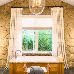 Photo of a beach style master bathroom in Santa Barbara with an undermount tub and grey floor.