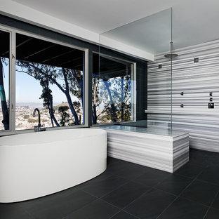 Immagine di una stanza da bagno minimalista con doccia a filo pavimento, vasca freestanding, pavimento nero e panca da doccia