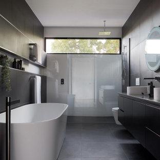 Modernes Badezimmer En Suite mit flächenbündigen Schrankfronten, schwarzen Schränken, freistehender Badewanne, grauen Fliesen, Aufsatzwaschbecken, grauer Waschtischplatte, Doppelwaschbecken, schwebendem Waschtisch, Nische, Duschnische, Wandtoilette, Porzellanfliesen, schwarzer Wandfarbe, Porzellan-Bodenfliesen, Quarzwerkstein-Waschtisch, schwarzem Boden und offener Dusche in Melbourne