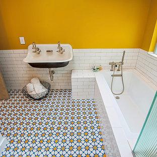 Exempel på ett mellanstort 60 tals badrum med dusch, med öppna hyllor, ett undermonterat badkar, en hörndusch, en toalettstol med separat cisternkåpa, vit kakel, stenkakel, gula väggar, cementgolv, ett avlångt handfat, bänkskiva i akrylsten, blått golv och dusch med gångjärnsdörr