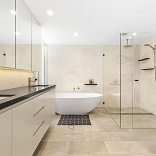 Design ideas for a mid-sized contemporary master bathroom in Sydney with flat-panel cabinets, beige cabinets, a freestanding tub, a double shower, beige tile, gray tile, beige walls, an undermount sink, grey floor, a hinged shower door and black benchtops.