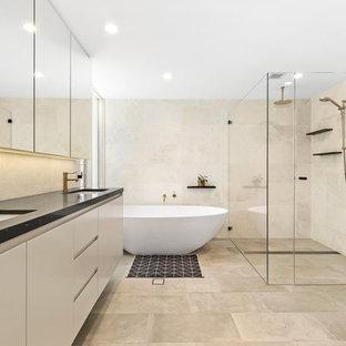 Idee per una stanza da bagno padronale design di medie dimensioni con ante lisce, ante beige, vasca freestanding, doccia doppia, piastrelle beige, piastrelle grigie, pareti beige, lavabo sottopiano, pavimento grigio, porta doccia a battente e top nero