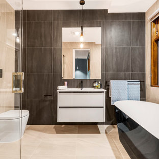 Inspiration for a contemporary 3/4 bathroom in Melbourne with flat-panel cabinets, white cabinets, a freestanding tub, a corner shower, a one-piece toilet, beige tile, gray tile, beige floor, a hinged shower door and white benchtops.