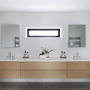 This is an example of a large modern ensuite bathroom in London with flat-panel cabinets, light wood cabinets, a freestanding bath, a walk-in shower, a one-piece toilet, beige tiles, porcelain tiles, grey walls, porcelain flooring, an integrated sink, engineered stone worktops, grey floors, a hinged door and white worktops.