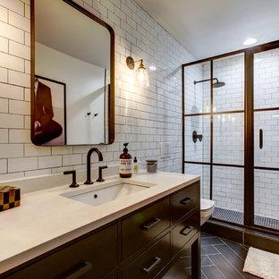 Idée de décoration pour une salle de bain urbaine de taille moyenne avec un placard en trompe-l'oeil, des portes de placard noires, un WC suspendu, un carrelage blanc, un carrelage métro, un mur blanc, un sol en carrelage de porcelaine, un lavabo encastré, un plan de toilette en quartz modifié, un sol marron, une cabine de douche à porte coulissante et un plan de toilette blanc.