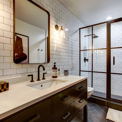 Mid-sized urban 3/4 white tile and subway tile porcelain tile and brown floor bathroom photo in Raleigh with furniture-like cabinets, black cabinets, a wall-mount toilet, white walls, an undermount sink, quartz countertops and white countertops