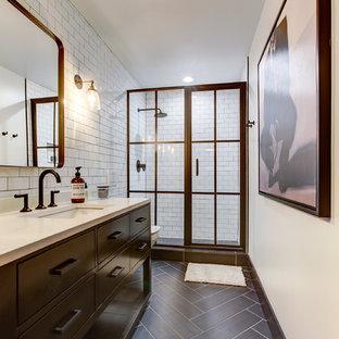 Inredning av ett industriellt mellanstort badrum, med möbel-liknande, svarta skåp, en vägghängd toalettstol, vit kakel, tunnelbanekakel, vita väggar, klinkergolv i porslin, ett undermonterad handfat, bänkskiva i kvarts, brunt golv, dusch med gångjärnsdörr och en dusch i en alkov