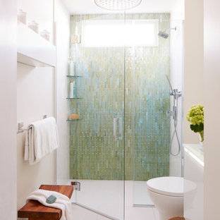 Inspiration for a small contemporary master bathroom in Boston with a curbless shower, a two-piece toilet, glass tile, white walls, porcelain floors, a wall-mount sink, glass benchtops, glass-front cabinets, white cabinets, green tile, white floor and a hinged shower door.