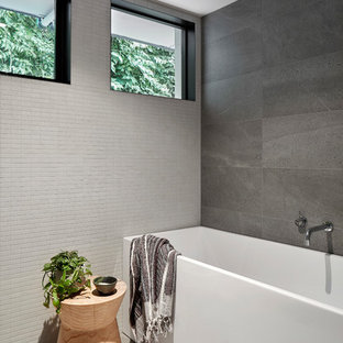Photo of a small contemporary kids bathroom in Melbourne with a freestanding tub, gray tile, grey floor, furniture-like cabinets, black cabinets, a shower/bathtub combo, a wall-mount toilet, ceramic tile, grey walls, cement tiles, an integrated sink, solid surface benchtops, an open shower, white benchtops, a single vanity and a floating vanity.