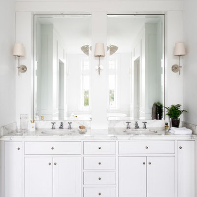 Elegant master white tile marble floor bathroom photo in Melbourne with an undermount sink, white cabinets, marble countertops, white walls and white countertops