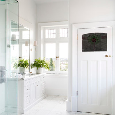 Inspiration for a timeless white tile marble floor corner shower remodel in Melbourne with an undermount sink, shaker cabinets, white cabinets, marble countertops and white walls