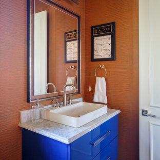 Immagine di una stanza da bagno minimalista con ante lisce, ante blu, WC monopezzo, pareti arancioni, pavimento in gres porcellanato, lavabo a bacinella, top in marmo, pavimento grigio e porta doccia a battente