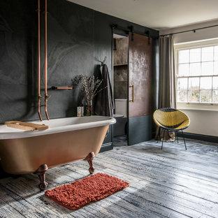 Immagine di una stanza da bagno padronale contemporanea con vasca con piedi a zampa di leone, piastrelle nere, pareti nere, pavimento in legno verniciato e top in rame