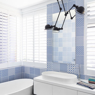This is an example of a contemporary bathroom in Brisbane with flat-panel cabinets, white cabinets, a freestanding tub, blue tile, a vessel sink, white benchtops, a single vanity and a floating vanity.