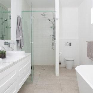 Неиссякаемый источник вдохновения для домашнего уюта: главная ванная комната среднего размера в стиле современная классика с фасадами в стиле шейкер, белыми фасадами, отдельно стоящей ванной, душем в нише, белой плиткой, керамогранитной плиткой, серыми стенами, полом из керамогранита, душем с распашными дверями, белой столешницей, тумбой под две раковины, подвесной тумбой, бежевым полом и панелями на части стены