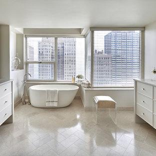 シカゴの大きいトランジショナルスタイルのおしゃれなマスターバスルーム (家具調キャビネット、白いキャビネット、白い壁、アンダーカウンター洗面器、ベージュの床、大理石の洗面台、置き型浴槽、アルコーブ型シャワー、ベージュのタイル、トラバーチンタイル、トラバーチンの床、開き戸のシャワー) の写真