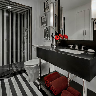 Alcove shower - mid-sized contemporary 3/4 black tile, black and white tile and white tile multicolored floor alcove shower idea in Chicago with open cabinets, a one-piece toilet, white walls, an undermount sink, a hinged shower door and black countertops