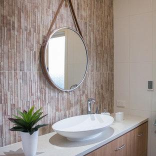 Modelo de cuarto de baño principal, de estilo zen, de tamaño medio, con armarios tipo mueble, puertas de armario de madera clara, bañera encastrada, ducha esquinera, sanitario de una pieza, baldosas y/o azulejos beige, baldosas y/o azulejos de porcelana, paredes beige, suelo de baldosas de porcelana, lavabo sobreencimera y encimera de laminado