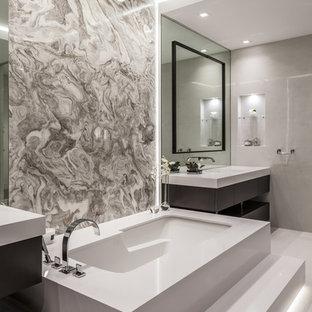 Idee per una grande stanza da bagno padronale minimal con ante lisce, ante in legno bruno, vasca sottopiano, zona vasca/doccia separata, WC monopezzo, piastrelle beige, piastrelle in ceramica, pareti beige, pavimento in cementine, lavabo integrato, pavimento beige e top bianco
