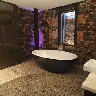 Foto på ett rustikt badrum, med ett fristående handfat, bänkskiva i kvarts, ett fristående badkar, en kantlös dusch, en toalettstol med hel cisternkåpa, brun kakel och porslinskakel