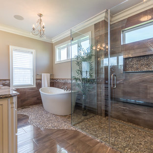 Bathroom - traditional beige tile and brown tile brown floor bathroom idea in Cleveland with raised-panel cabinets, white cabinets, beige walls, an undermount sink, a hinged shower door and brown countertops