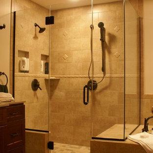 他の地域の中くらいのおしゃれなマスターバスルーム (落し込みパネル扉のキャビネット、濃色木目調キャビネット、ドロップイン型浴槽、茶色いタイル、セラミックタイル、セラミックタイルの床、人工大理石カウンター、ベージュの壁、ベージュの床、開き戸のシャワー、ベージュのカウンター、オープン型シャワー、アンダーカウンター洗面器) の写真