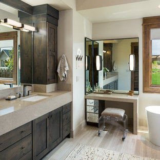 Large mountain style limestone floor and beige floor freestanding bathtub photo in Other with shaker cabinets, white walls, an undermount sink, engineered quartz countertops and dark wood cabinets