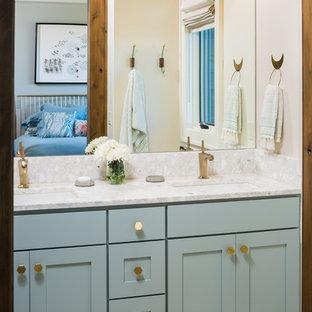 Imagen de cuarto de baño rural, grande, con armarios estilo shaker, puertas de armario turquesas, paredes amarillas, suelo de baldosas de porcelana, lavabo bajoencimera, encimera de piedra caliza y suelo blanco