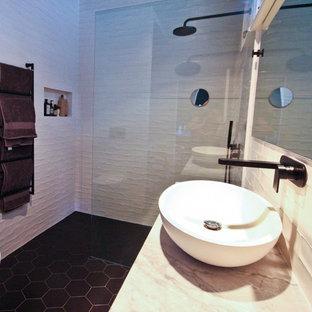 Immagine di una stanza da bagno padronale minimalista di medie dimensioni con ante lisce, ante nere, doccia aperta, WC sospeso, piastrelle bianche, piastrelle in ceramica, pareti bianche, pavimento in sughero, lavabo a bacinella, top in marmo, pavimento nero, doccia aperta e top bianco