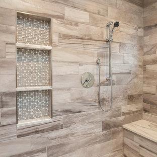 デンバーの巨大なコンテンポラリースタイルのおしゃれなマスターバスルーム (フラットパネル扉のキャビネット、ヴィンテージ仕上げキャビネット、置き型浴槽、オープン型シャワー、ベージュのタイル、セラミックタイル、グレーの壁、無垢フローリング、アンダーカウンター洗面器、御影石の洗面台) の写真