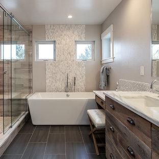 Immagine di un'ampia stanza da bagno padronale rustica con ante lisce, ante con finitura invecchiata, vasca freestanding, doccia aperta, piastrelle beige, piastrelle in ceramica, pareti grigie, lavabo sottopiano e porta doccia scorrevole