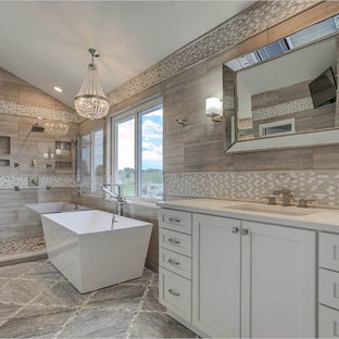 Design ideas for a large contemporary ensuite bathroom in Denver with shaker cabinets, white cabinets, a freestanding bath, a corner shower, beige tiles, brown tiles, porcelain tiles, beige walls, ceramic flooring, a submerged sink, brown floors and a hinged door.